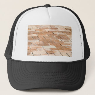 Pavement of brown tiles - close up view trucker hat