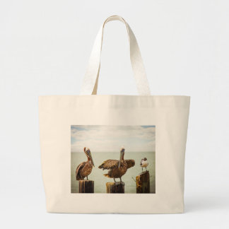 Pelicans perched on posts large tote bag