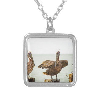 Pelicans perched on posts silver plated necklace