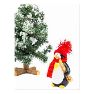 Penguin figurine with skis and christmas tree postcard