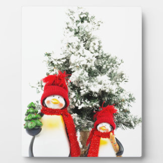 penguin figurines with christmas tree in winter plaque