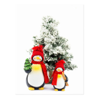 penguin figurines with christmas tree in winter postcard