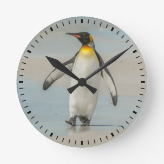 Penguin walking on the beach clocks