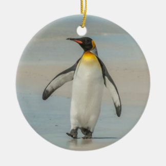 Penguin walking on the beach round ceramic ornament