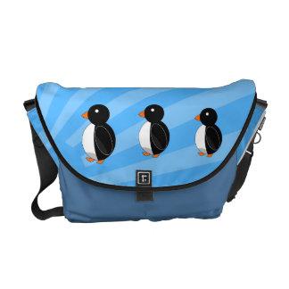 Penguins on blue sunburst messenger bag