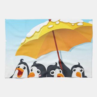 Penguins standing under umbrella kitchen towel