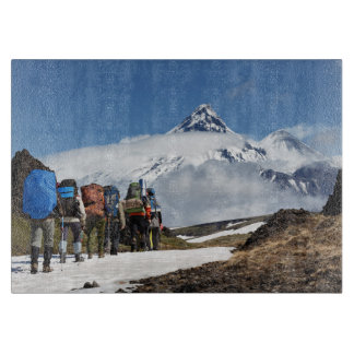 People climbing on mount on background volcanoes cutting board