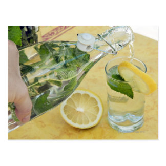 Person pouring water (mint-filled) into a glass postcard
