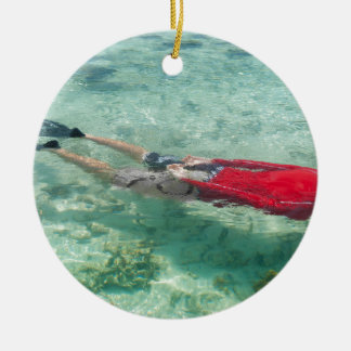Person snorkeling in clear water round ceramic ornament
