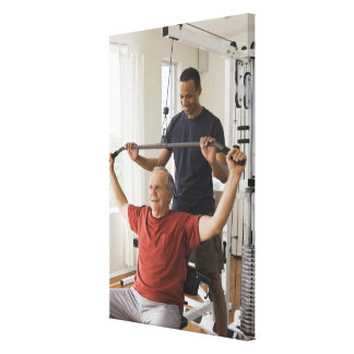 Personal trainer with man in home gym canvas print