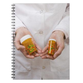Pharmacist holding pill bottles spiral notebooks