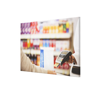 Pharmacist holding security device for customer stretched canvas print