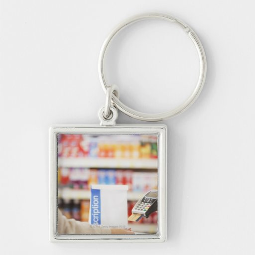 Pharmacist holding security device for customer key chains