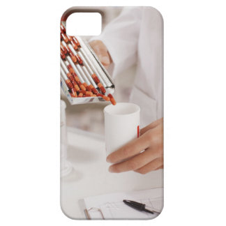 Pharmacist in drug store measuring pills into iPhone 5 cover