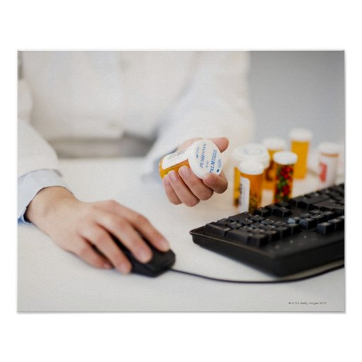 Pharmacist with pill bottles at computer poster