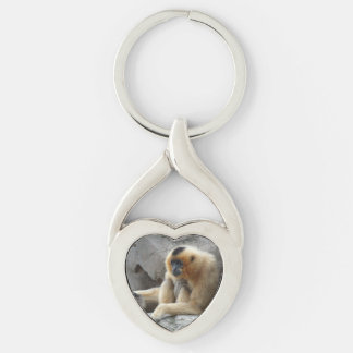 Photo of Orange and Black Gibbon Relaxing on Cliff Silver-Colored Twisted Heart Keychain