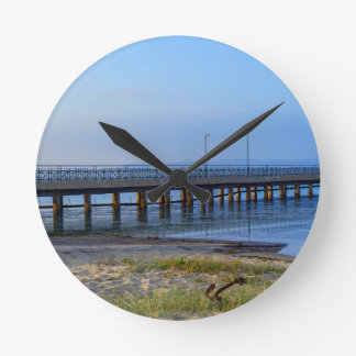 Photo of pier in sunset with anchor round clock
