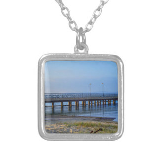 Photo of pier in sunset with anchor silver plated necklace