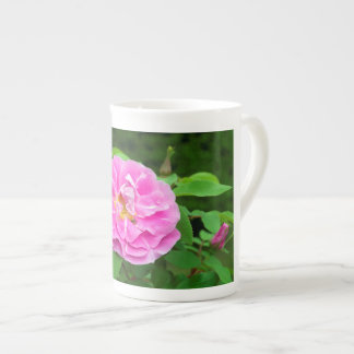 Photograph of pink rose blossom with small bee. tea cup