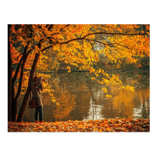 Photographer at lake in autumn postcard