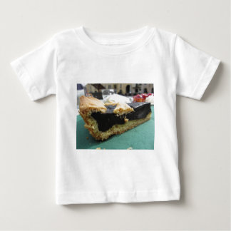 Piece of chocolate cake on green paper napkin baby T-Shirt