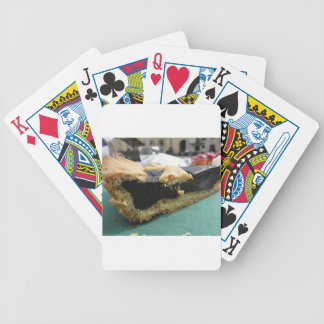 Piece of chocolate cake on green paper napkin bicycle playing cards
