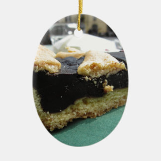 Piece of chocolate cake on green paper napkin ceramic ornament