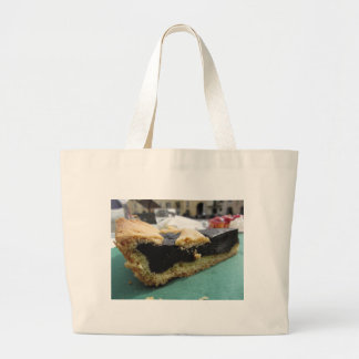 Piece of chocolate cake on green paper napkin large tote bag