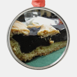 Piece of chocolate cake on green paper napkin metal ornament