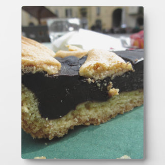 Piece of chocolate cake on green paper napkin plaque