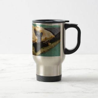 Piece of chocolate cake on green paper napkin travel mug