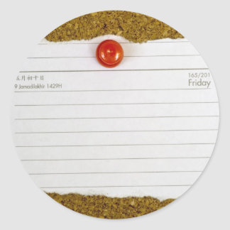 Piece of paper pegged to a cork board round sticker