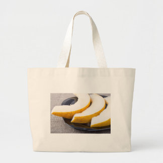 Pieces yellow melon on a black plate large tote bag