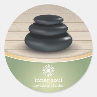 Pierres de massage sur le vert sauge en bois de sticker rond