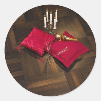 Pillows, candlesticks and champagne on dark parque classic round sticker