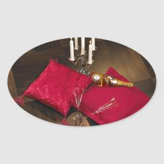 Pillows, candlesticks and champagne on dark parque oval sticker