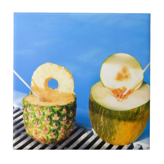 Pineapple and melon fruit with straws at pool ceramic tiles