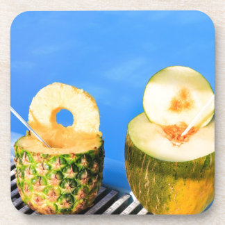 Pineapple and melon fruit with straws at pool drink coasters