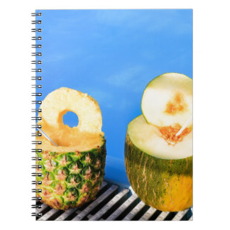 Pineapple and melon fruit with straws at pool notebooks