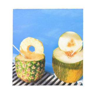 Pineapple and melon fruit with straws at pool notepads