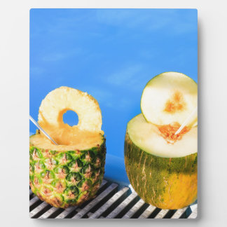 Pineapple and melon fruit with straws at pool plaque