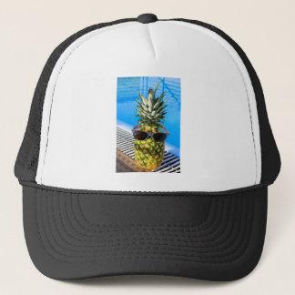 Pineapple wearing sunglasses at swimming pool trucker hat