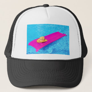 Pink air mattrass with hat in swimming pool
