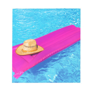 Pink air mattrass with hat in swimming pool notepad