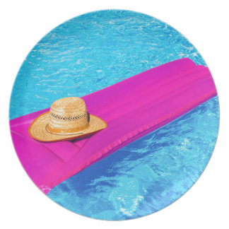 Pink air mattrass with hat in swimming pool party plates