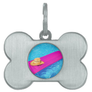 Pink air mattrass with hat in swimming pool pet ID tag
