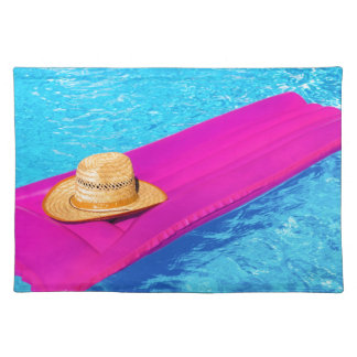 Pink air mattrass with hat in swimming pool placemat
