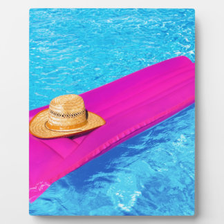 Pink air mattrass with hat in swimming pool plaque