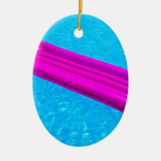 Pink air mattress on water of swimming pool ceramic oval ornament