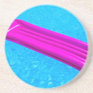 Pink air mattress on water of swimming pool coaster